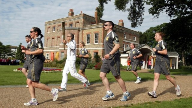 The Olympic Torch is carried past Valentines Mansion